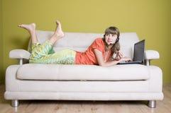 Chica joven de la belleza con la computadora portátil Fotografía de archivo libre de regalías