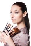 Chica joven de la belleza con los cepillos del maquillaje Natural compense a la mujer morena con los ojos del bleu Cara hermosa m Imagen de archivo libre de regalías