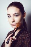 Chica joven de la belleza con los cepillos del maquillaje Natural compense a la mujer morena con los ojos del bleu Cara hermosa m fotografía de archivo