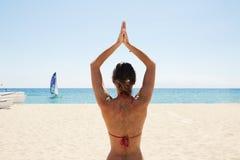 Chica joven de la foto que hace la playa de la yoga Mujer de la aptitud que gasta el mar al aire libre del tiempo activo Océano d Foto de archivo