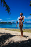 Chica joven de la foto que se relaja en el equipo que bucea de la playa El gasto sonriente de la mujer enfría la isla al aire lib Fotos de archivo libres de regalías