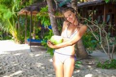 Chica joven de la foto que se relaja en la playa con el coco El gasto sonriente de la mujer enfría la isla al aire libre de Bali  Foto de archivo