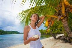 Chica joven de la foto que se relaja en la playa con las flores en la puesta del sol El gasto sonriente de la mujer enfría la isl Imagenes de archivo