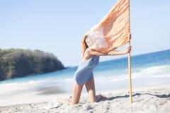 Chica joven de la foto que se relaja en la playa que sostiene la bandera Verano al aire libre sonriente del tiempo de la frialdad Foto de archivo