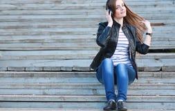 Chica joven de la moda con los auriculares Imagenes de archivo