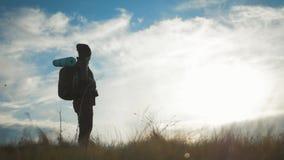 Chica joven de la silueta con la mochila que disfruta de puesta del sol desde arriba de la monta?a Viajero tur?stico en la puesta metrajes