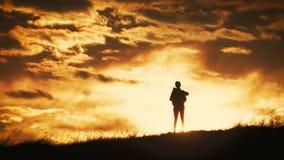 Chica joven de la silueta con la mochila que disfruta de puesta del sol desde arriba de la monta?a Viajero tur?stico en la puesta almacen de metraje de vídeo