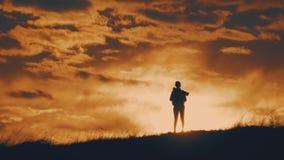 Chica joven de la silueta con la mochila que disfruta de puesta del sol desde arriba de la monta?a Viajero tur?stico en la puesta almacen de video