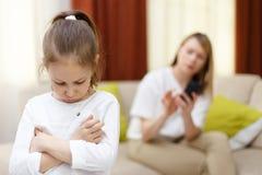 Chica joven de la tristeza Retrato de la hija aburrida con la madre que usa el teléfono móvil en cama Imagen de archivo