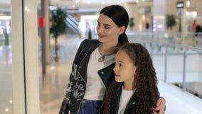 Chica joven de moda con una hermana más joven que camina en la alameda y hacer compras almacen de metraje de vídeo