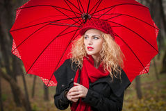 Chica joven de moda hermosa con el paraguas rojo, el casquillo rojo y la bufanda roja en el parque Fotos de archivo