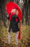 Chica joven de moda hermosa con el paraguas rojo, el casquillo rojo y la bufanda roja en el parque Imágenes de archivo libres de regalías