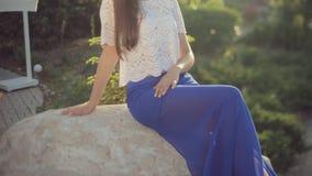 Chica joven de moda que se sienta en una piedra en metrajes