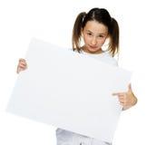Chica joven de moda que se sostiene a una tarjeta en blanco Fotos de archivo libres de regalías