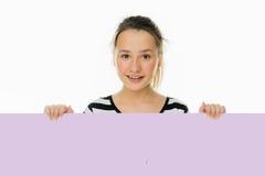 Chica joven de moda que se sostiene a una tarjeta en blanco Fotografía de archivo libre de regalías