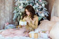 Chica joven de pelo largo encantadora que busca un regalo para el backg Imagen de archivo libre de regalías