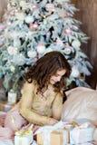 Chica joven de pelo largo encantadora que busca un regalo para el backg Foto de archivo