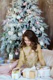 Chica joven de pelo largo encantadora que busca un regalo y un i sonriente Fotografía de archivo libre de regalías