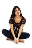 Chica joven de pensamiento que se sienta en el piso, mirando para arriba Foto de archivo