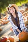 Chica joven de risa con una carretilla en el remiendo de la calabaza Imagenes de archivo