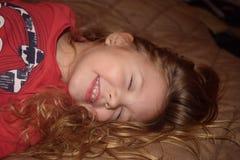 Chica joven de risa feliz que salta en la cama fotos de archivo libres de regalías