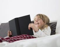 Chica joven de risa que lee un libro Fotos de archivo libres de regalías