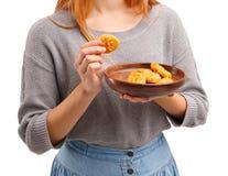 Chica joven de Smilling que se sostiene en pepitas de pollo de las manos Concepto del alimento Imagen de archivo libre de regalías