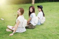 Chica joven de tres Asia con el bolso en parque foto de archivo