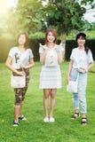 Chica joven de tres Asia con el bolso en parque fotos de archivo