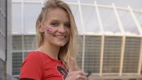 Chica joven de un fanático del fútbol rubio de Inglaterra, sonrisa, mostrando como muestra, concepto del campeonato, estadio en almacen de video