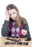 Chica joven decepcionada con la mano en la frente que mira la teja del dominó aislada en el fondo blanco Imagenes de archivo