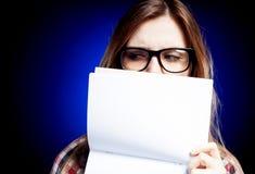 Chica joven decepcionada con sostenerse de los vidrios del empollón   Fotos de archivo libres de regalías