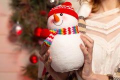 Chica joven del Año Nuevo con humor del día de fiesta en interior de la Navidad con el árbol y los juguetes decorativos divertido Imagen de archivo
