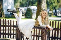 Chica joven del adolescente que miente en el banco en un parque Fotos de archivo libres de regalías