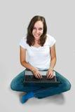 Chica joven del estudiante con el ordenador portátil en fondo gris Foto de archivo