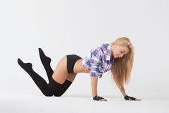 Chica joven del gimnasta de la muchacha que hace los ejercicios gimnásticos aislados Imagenes de archivo