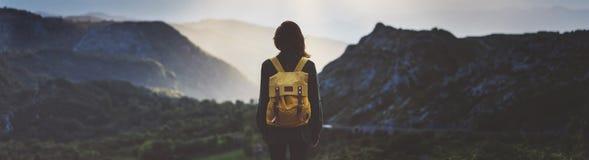 Chica joven del inconformista con la mochila brillante que disfruta de puesta del sol en pico de la montaña de niebla Viajero tur imagen de archivo libre de regalías