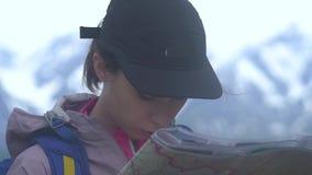 Chica joven del inconformista con la mochila en el pico de la montaña que mira el mapa Viajero turístico en la opinión del paisaj almacen de metraje de vídeo