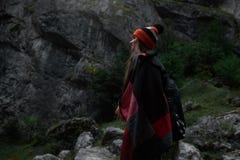 Chica joven del inconformista con la mochila en montañas Foto de archivo