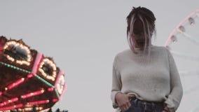 Chica joven del inconformista en los vidrios que colocan la atracción cercana del carrusel en parque del amusment almacen de metraje de vídeo