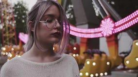 Chica joven del inconformista en los vidrios que colocan la atracción cercana de la oscilación en parque del amusment metrajes