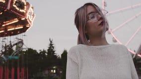Chica joven del inconformista en los vidrios que presentan cerca de la atracción del carrusel en parque del amusment almacen de metraje de vídeo