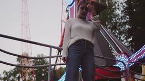 Chica joven del inconformista en los vidrios que presentan cerca de la atracción del oscilación en parque del amusment almacen de video