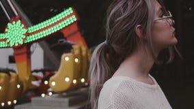 Chica joven del inconformista en los vidrios que presentan cerca de la atracción de la oscilación en parque del amusment almacen de video