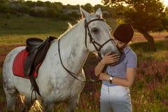 Chica joven del jinete que acaricia y que abraza el caballo blanco en puesta del sol de la tarde Foto de archivo libre de regalías