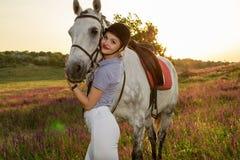 Chica joven del jinete que acaricia y que abraza el caballo blanco en puesta del sol de la tarde Fotos de archivo libres de regalías