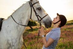 Chica joven del jinete que acaricia y que abraza el caballo blanco en puesta del sol de la tarde Imagen de archivo libre de regalías