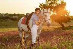 Chica joven del jinete que acaricia y que abraza el caballo blanco en puesta del sol de la tarde Llamarada de Sun Imagenes de archivo