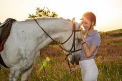 Chica joven del jinete que acaricia y que abraza el caballo blanco en puesta del sol de la tarde Llamarada de Sun Fotografía de archivo