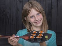 Chica joven del retrato con el sushi, cierre para arriba Imagenes de archivo